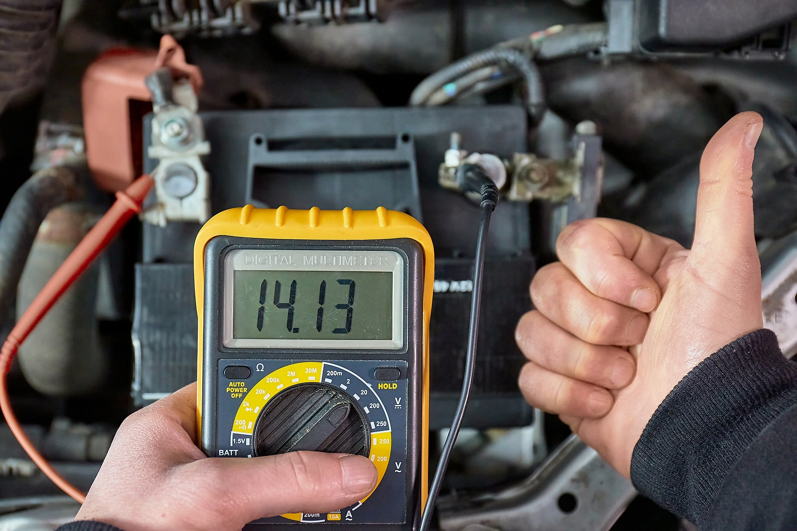 mechanic showing how to test a starter solenoid with a multimeter